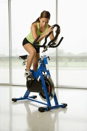 closed club: Mid adult Asian woman pedaling exercise bicycle indoors. Stock Photo