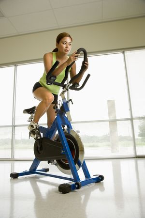 Mid adult Asian woman pedaling exercise bicycle indoors. Stock Photo