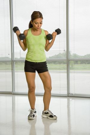 Mid adult Asian woman standing lifting dumbbells. photo