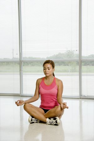 Mid adult Asian woman sitting in yoga lotus position with eyes closed. Stock Photo - 1850158