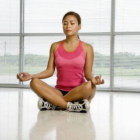 Mid adult Asian woman sitting in yoga lotus position with eyes closed. Stock Photo - 1850176