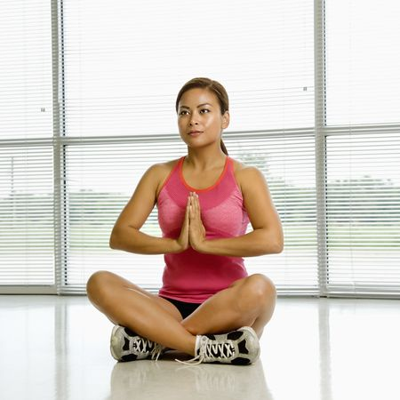 Mid adult Asian woman sitting in yoga lotus position with palms together. Stock Photo - 1850152