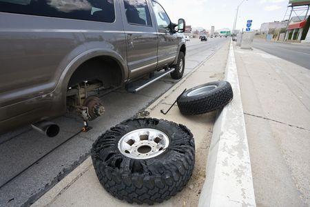 needing: Vehicle brokendown along roadside with damaged tire needing replacement.