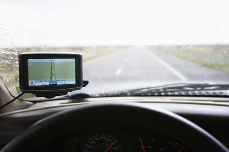 Vehicle dashboard with GPS and view through windshield of highway ahead. Stock Photo