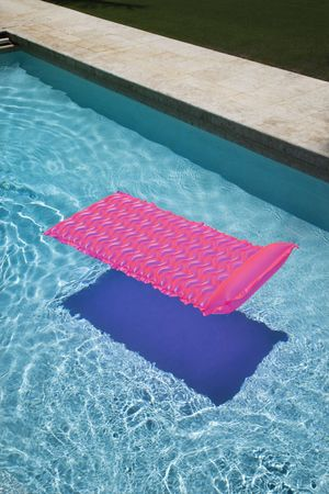 inground: Pink lounge float in empty swimming pool.