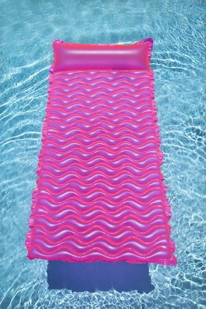 inground: Pink lounge float in empty swimming pool with rippling blue water. Stock Photo