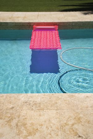 inground: Pink float and vacuum hose in swimming pool. Stock Photo