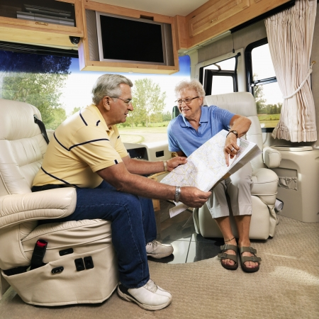 motorhome: Senior couple sitting in RV looking at map and smiling. Stock Photo