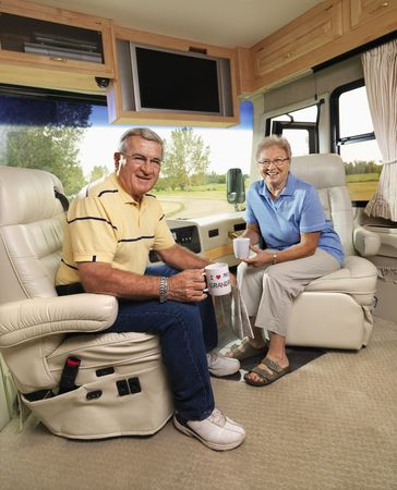 women coffee: Senior couple sitting in RV holding coffee cups and smiling. Stock Photo