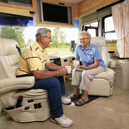 motorhome: Senior couple sitting in RV holding coffee cups and smiling. Stock Photo