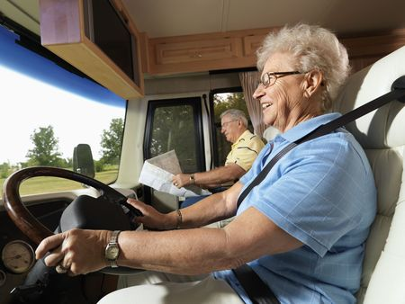 Senior adult woman driving RV and smiling while man reads map in passenger seat.