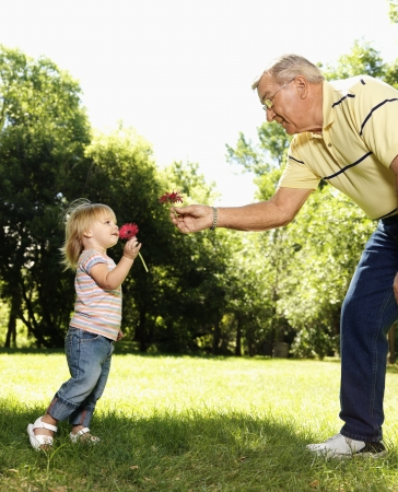 granddaughters: Grandfather and granddaughter holding flowers and smelling. Stock Photo