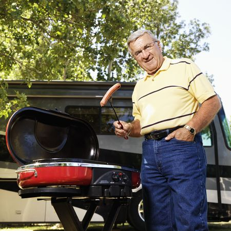 senior adult man: Senior adult man grilling hotdogs with RV in background. Stock Photo