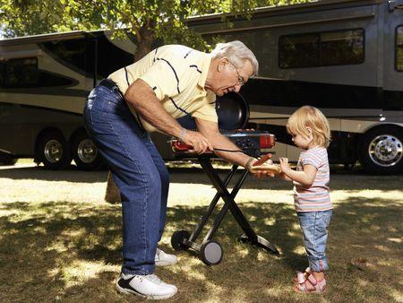 hot grill: Grandfather giving granddaughter hotdog by RV.
