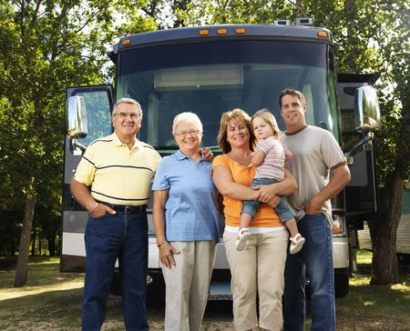 Portrait of three generation Caucasian family standing in front of recreational vehicle smiling and looking at viewer. photo