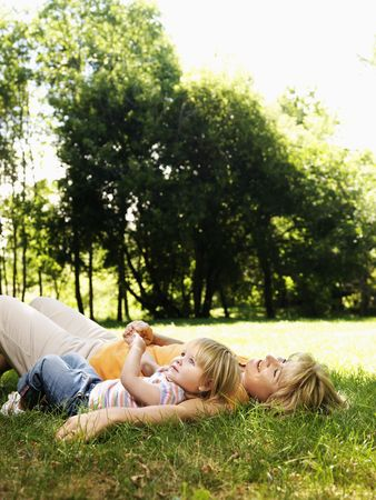 Caucasian mid adult woman with toddler daughter lying in grass at park relaxing. photo