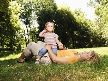 Caucasian mid adult woman lying in grass at park with toddler daughter seated on her lap. photo