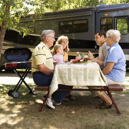 Three generation Caucasian family seated at picnic table in front of recreational vehicle talking. photo