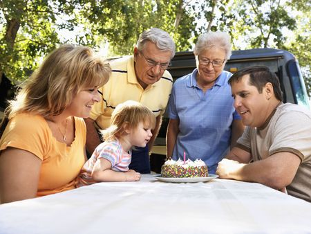 three generation: Three generation Caucasian family seated at picnic table celebrating female childs birthday with cake.