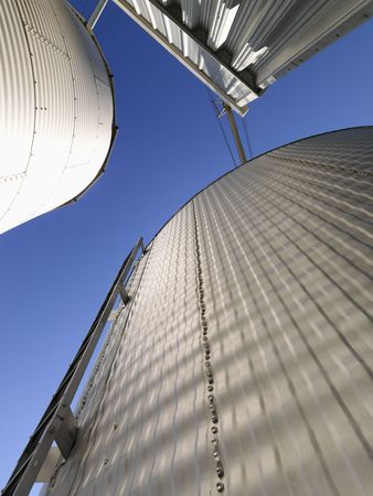 Low angle view of metal grain storage silos against blue sky.