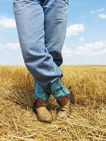 cowboy boots: Cowboy standing in harvested crop field wearing funky cowboy boots.