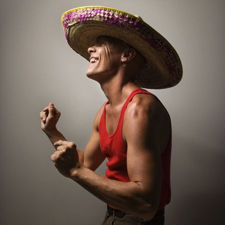 snapping fingers: Portrait of a Mid-adult Caucasian male wearing sombrero snapping fingers.