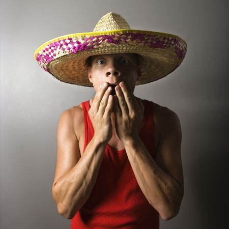 gasp: Portrait of a mid-adult Caucasian male wearing sombrero with hands over mouth.