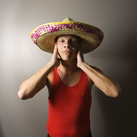 hands over ears: Portrait of a mid-adult Caucasian male wearing sombrero with hands over ears.