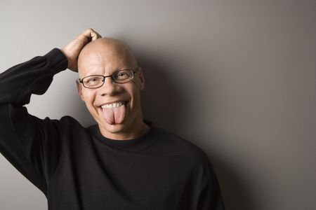 Portrait of mid-adult Caucasian male sticking out tongue. Stock Photo - 1850459