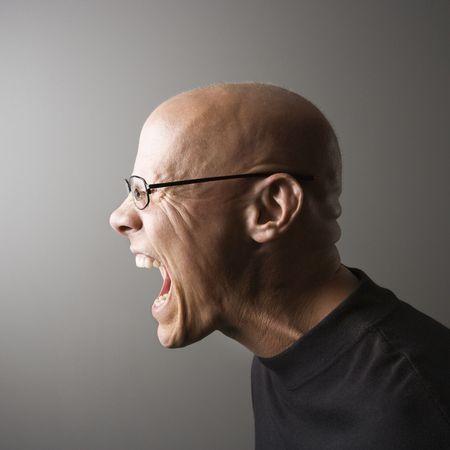 Profile portrait of mid-adult Caucasian male screaming. photo