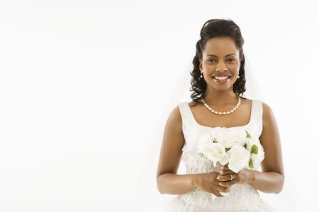 Mid-adult African-American bride holding bouquet on white background.