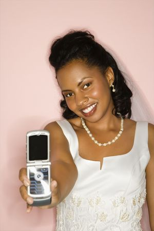Mid-adult African-American bride holding cellphone out towards viewer with a pink background. Stock Photo - 1858978