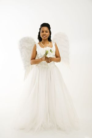 Angelic mid-adult African-American bride holding a bouquet on white background. Stock Photo - 1858830