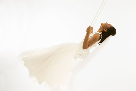 Mid-adult African-American bride swinging with white background. Stock Photo - 1858805
