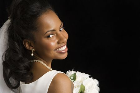 Portrait of a mid-adult African-American bride on black background. Stock Photo