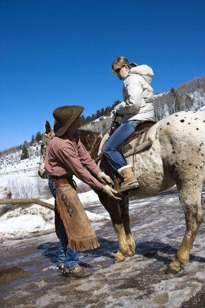 Caucasian male wrangler helping young adult Caucasian female on horseback. Stock Photo - 1859166