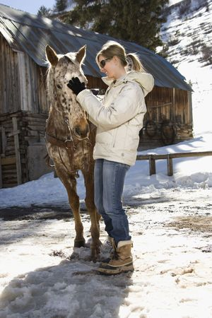 petting: Young adult Caucasian woman petting horse with stable in background in winter.