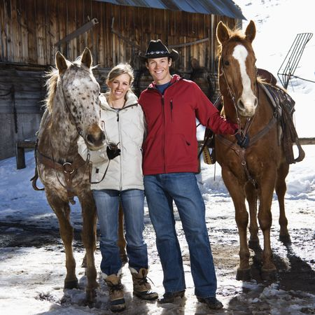 Caucasian couple holding horses in winter with stable in background. photo