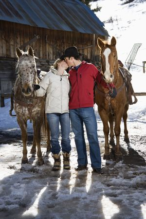 Young adult Caucasian couple kissing and holding horses with stable in background.