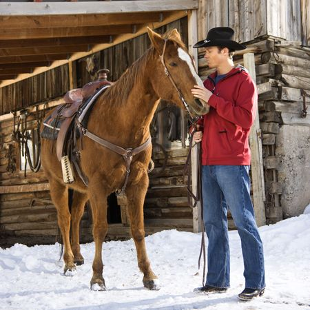 petting: Young Caucasian man in western attire petting his horse with stable in background.