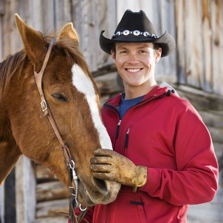 petting: Young Caucasian man in cowboy hat petting his horse. Stock Photo