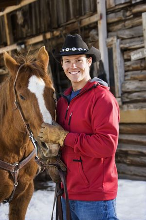 Young adult Caucasian male in cowboy hat petting horse. Stock Photo