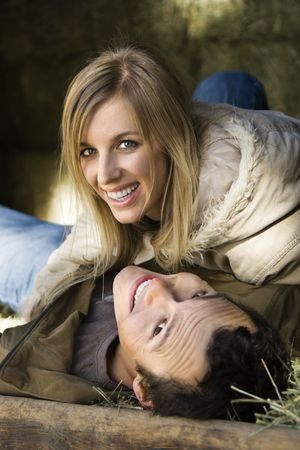 Young adult Caucasian couple lying in hay and smiling up at viewer.