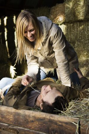 Young adult Caucasian woman playfully leaning over man lying in hay. photo