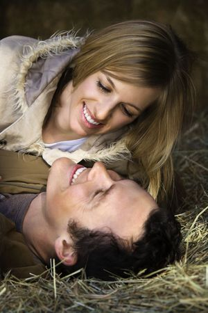 Young adult Caucasian couple lying in hay. photo