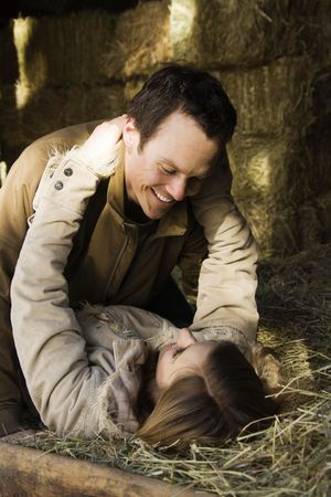 Young adult Caucasian couple laying in hay embracing. photo
