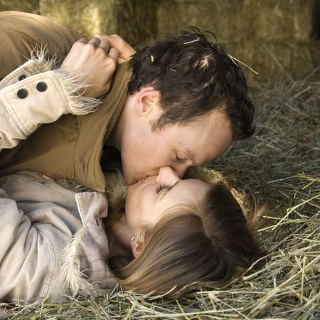 passionate kissing: Young adult Caucasian couple lying down in hay kissing.