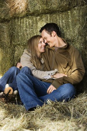 Young adult Caucasian couple sitting on hay hugging and smiling at each other. photo