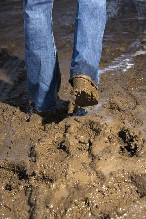 muddy clothes: Close up of person walking in mud wearing jeans and boots. Stock Photo
