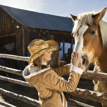 petting: Young Caucasian woman petting horse with stable in background. Stock Photo